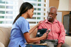 nurse checking the blood pressure of a senior man