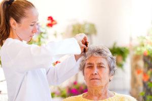 caregiver assisting a senior woman