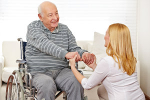 caregiver holding the hands of the old man